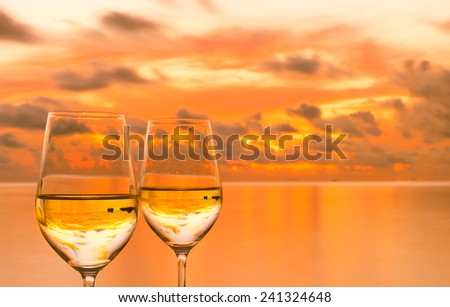 Glasses of white wine against sunset  - stock photo
