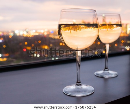 Glasses of white wine with city view - stock photo