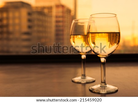 Glasses of white wine with city view.  - stock photo