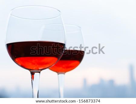 Glasses of wine against city skyline - stock photo