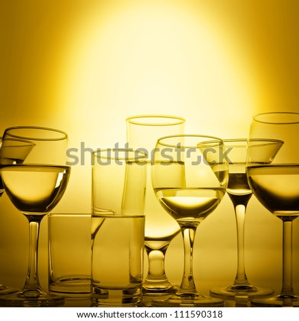 Glasses  of wine in gold color on silhouette of black on a bright Sunny background - stock photo
