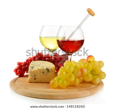 Glasses of wine, tasty blue cheese and grape on cutting board, isolated on white