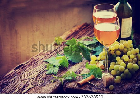 Glasses of wine with bottle,corks and grapes over rustic wooden background - stock photo