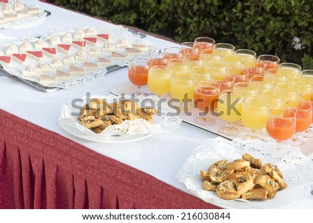 Glasses of with exotic drinks and cookies on the decorated table. - stock photo