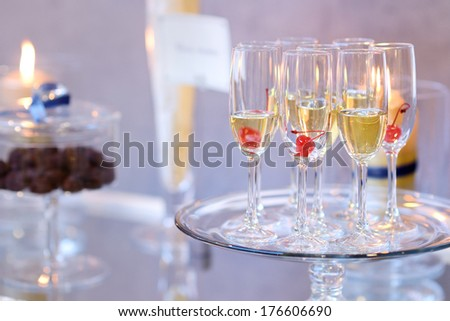 Glasses of with pink champagne decorated with cherries