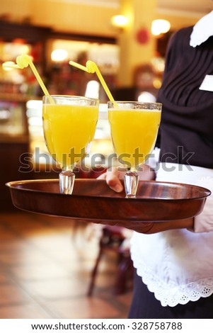 Glasses of yellow cocktails on tray in waiter hands in cafe