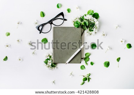Glasses, old book, pen and branches with leaves and flowers on white background. Flat lay composition - stock photo
