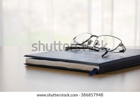 Glasses on a book and table with nature background - stock photo