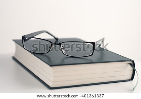 Glasses on a book, isolated on white