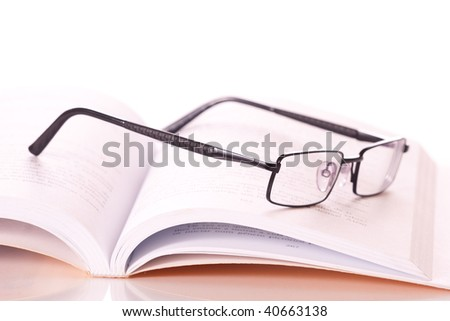 glasses on a book, isolated on white background - stock photo