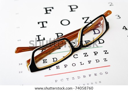 Glasses on a eye sight test chart. hard contrast! - stock photo