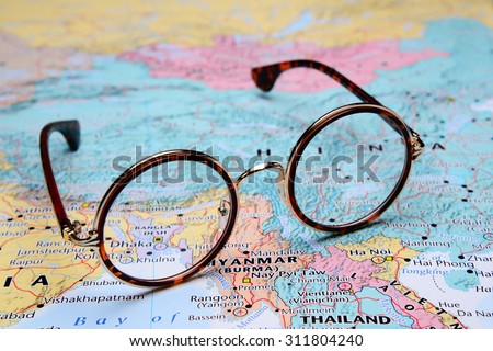 Glasses on a map of Asia - Dhaka  - stock photo
