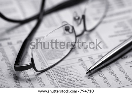 Glasses on a newspaper with a pen. Black and white