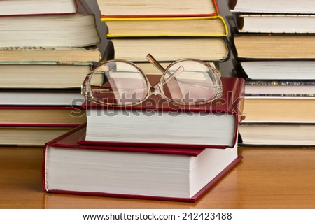 Glasses on a pile of red books - stock photo