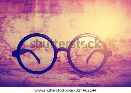 Glasses on an old map with vintage style. - stock photo