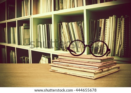 glasses on books with blur perspective bookshelf background - stock photo