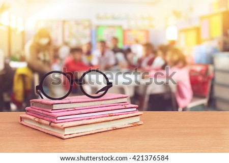 glasses on books with blur student in classroom background - stock photo
