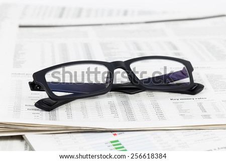 Glasses on business newspapers - stock photo