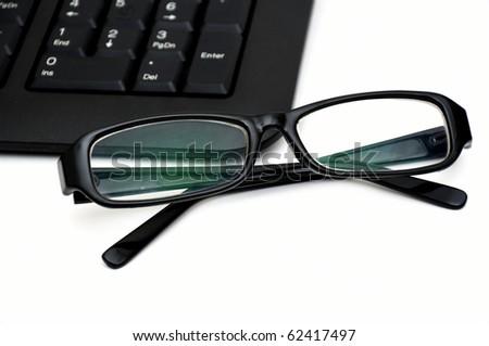 glasses on computer keyboard - stock photo