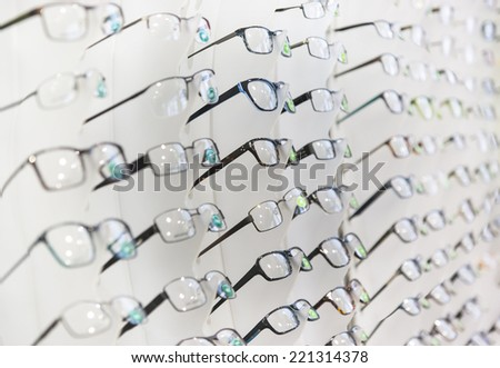 Glasses on display on wall in store - stock photo