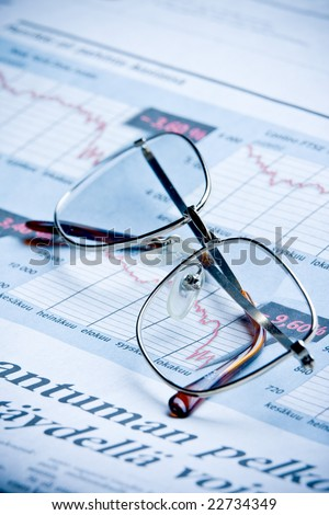 glasses on financial diagram. business concept