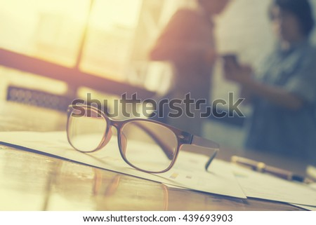 glasses on office desk and office supplies.office desk table with a lot of things on it.and business people meeting and writing business plan in background,copy space.vintage color.selective focus.