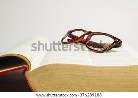 Glasses on opened dictionary - stock photo