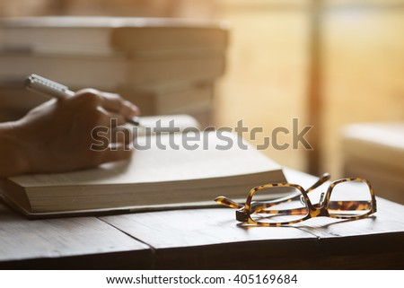 glasses on opening book,morning light effect. - stock photo