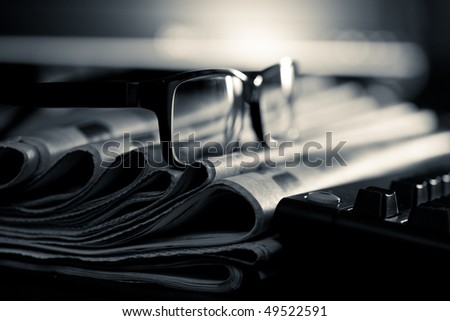 Glasses on stack of newspapers, very shallow focus - stock photo