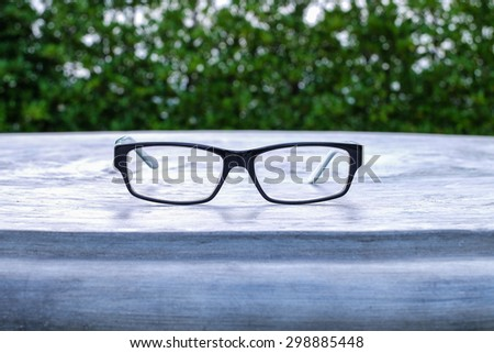 Glasses on table in the park with blurred tree background