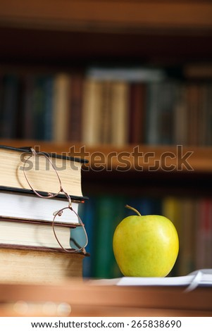 glasses on the books and green apple - stock photo