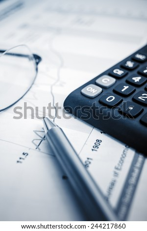 glasses on the finance chart on the desk. - stock photo
