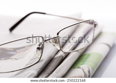Glasses on the newspapers macro - stock photo