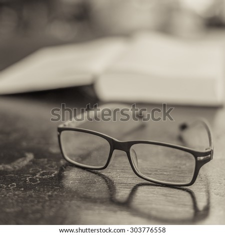 Glasses on the table and a book in information time
