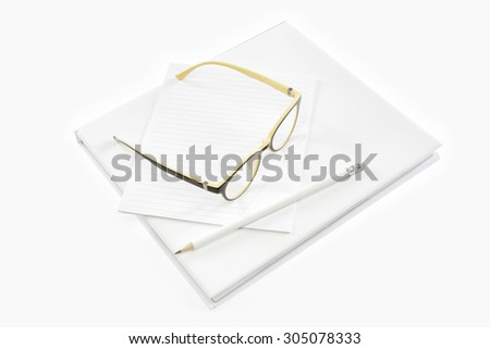 glasses, pencil and notepads on  book with isolated background