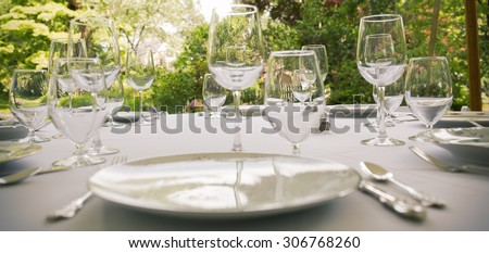 Glasses, plates, silverware on a table for a party.