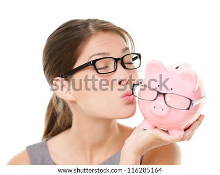 Glasses sale concept. Happy woman kissing piggy bank wearing eyewear glasses. Mixed race Asian Chinese / Caucasian female model isolated on white background. - stock photo