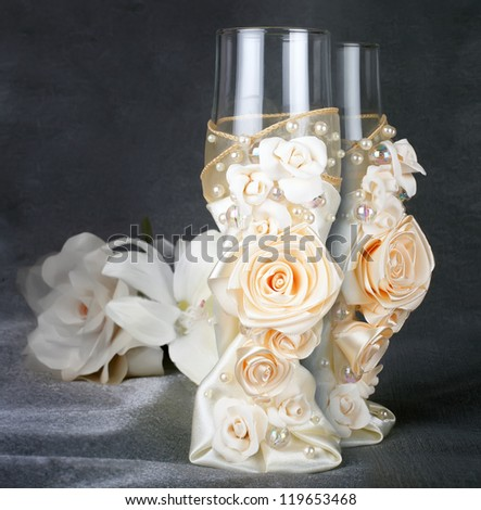 glasses two glasses of wedding richly embellished with organza beige pearl-colored and glass beads pearls and artificial roses on a background of tea rose on the gray dark pearl background - stock photo
