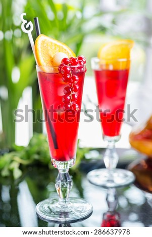 Glasses with alcohol cocktail with cranberry juice on a table in a restaurant with a creative composition and decoration of pieces of orange and fresh berries. soft focus - stock photo