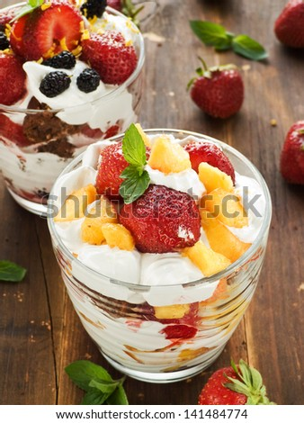 Glasses with berry parfait and whipped cream. Shallow dof. - stock photo