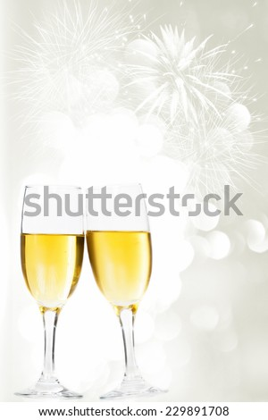 Glasses with champagne against fireworks and sparkling holiday background - stock photo