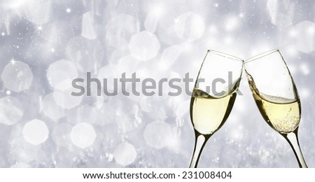 Glasses with champagne against sparkling holiday background - stock photo