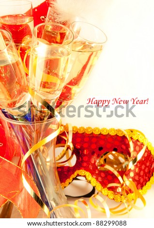 Glasses with champagne and a New Year's mask, a carnival - stock photo