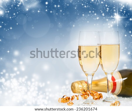 Glasses with champagne and bottle over sparkling holiday background - stock photo