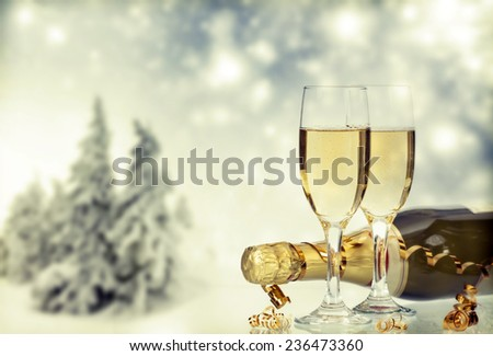 Glasses with champagne and bottle, snow cowered pine trees in the background - stock photo