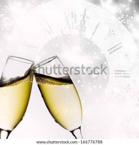 Glasses with champagne and clock close to midnight - stock photo