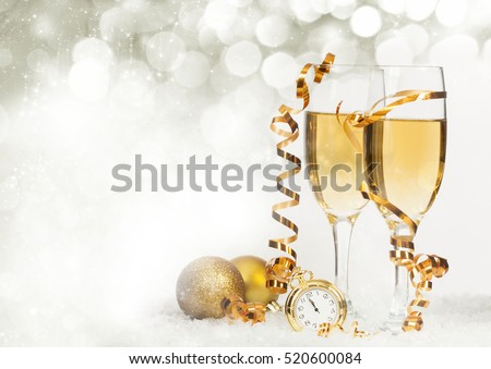 Glasses with champagne and golden Christmas balls against holiday lights - New Year background