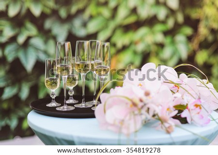 glasses with champagne on round table  - stock photo