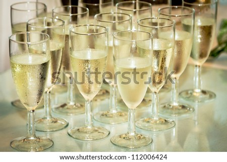 Glasses with champagne on the party table - stock photo