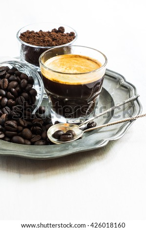 Glasses with coffee beans, ground coffee and espresso coffee drink on rustic wooden table,  selective focus - stock photo